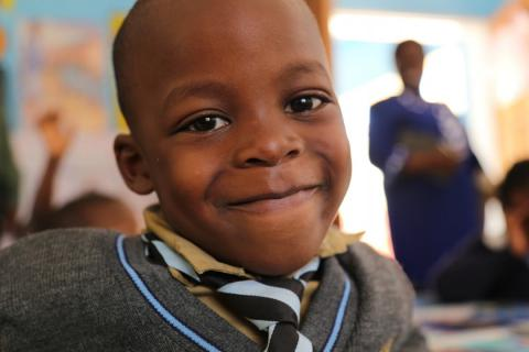 A school children smiles at the camera. Avondale Infant School, Zimbabwe